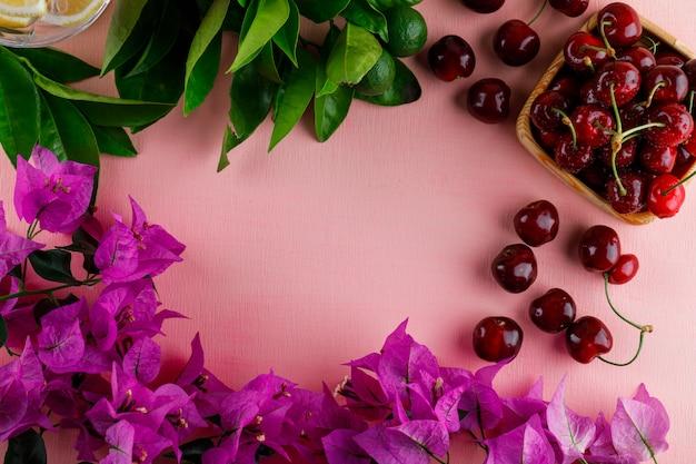 Cerezas con flores, limones, hojas, en un plato de madera sobre una superficie rosa, vista superior