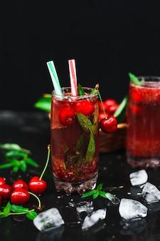 Cerezas frescas colocadas en una cesta y cerezas negras con salpicaduras de agua.