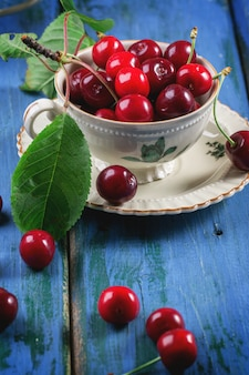 Cerezas frescas en una taza de té vintage