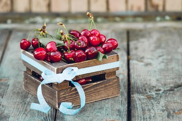Cerezas con hojas en caja de madera vintage sobre mesa de madera rústica. copie el espacio.