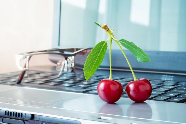 Cerezas jugosas rojas en el fondo de una computadora portátil. descanso en horario de oficina