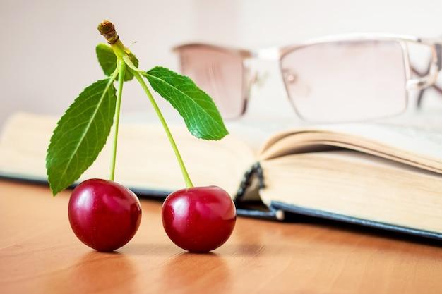 Cerezas maduras en el fondo de un libro abierto. descanso durante la lectura para comer