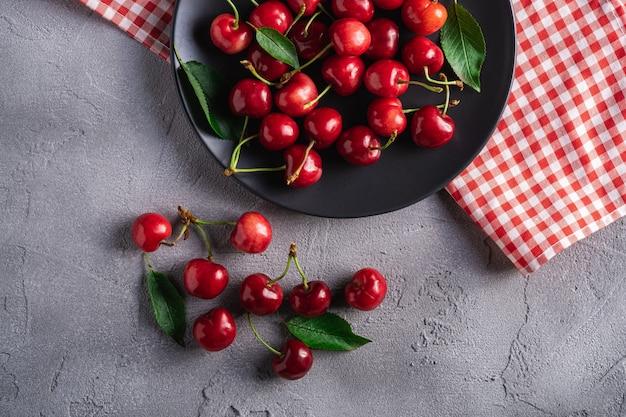 Cerezas maduras frescas con hojas verdes en un plato negro con mantel rojo