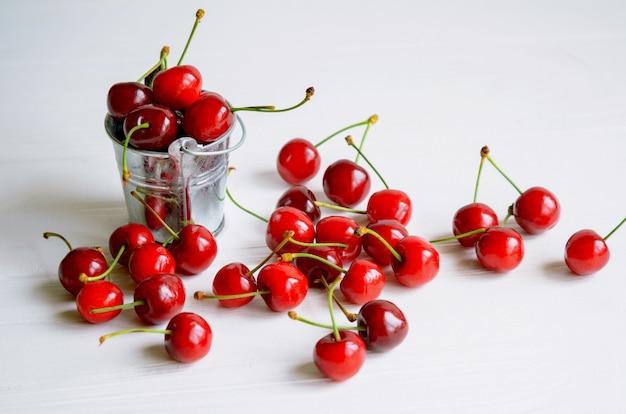 Cerezas maduras en un pequeño cubo de lata sobre madera blanca, postre sabroso y saludable