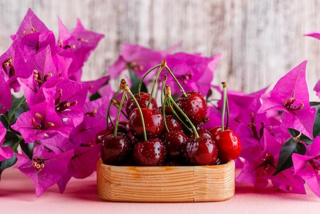 Cerezas en una placa de madera con vista lateral de flores sobre superficie rosada y sucia