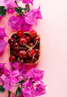Las cerezas en un plato de madera con flores planas yacían sobre una superficie rosa
