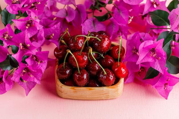Cerezas en un plato de madera con flores vista de ángulo alto sobre una superficie rosa