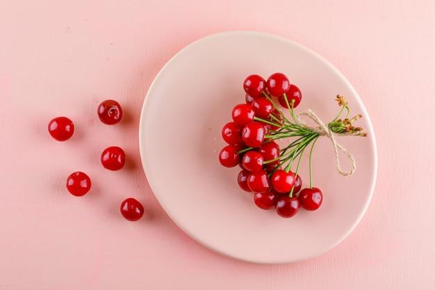 Las cerezas en un plato plano yacían sobre una mesa rosa