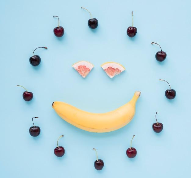 Cerezas rojas dispuestas en un marco circular con cara sonriente hecha con plátano y pomelo sobre fondo azul