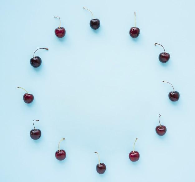 Cerezas rojas dispuestas en marco circular sobre fondo azul
