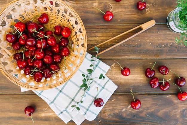 Cerezas rojas frescas en un recipiente de mimbre sobre fondo de madera