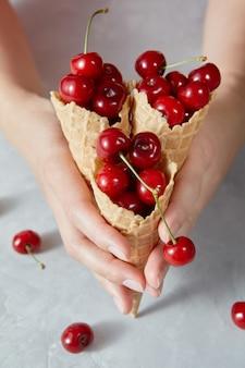 Cerezas rojas maduras jugosas en los conos de oblea
