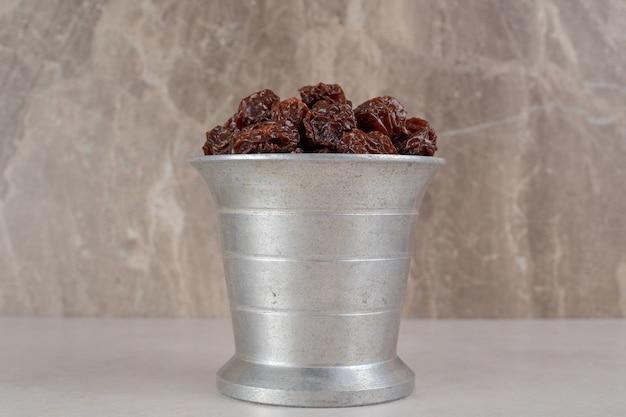 Cerezas secas de color marrón en un cubo metálico.
