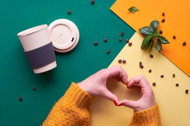 Cero desperdicio de café. eco amigable reutilizable tazas de café, manos en suéter naranja que muestra el signo del corazón. plano geométrico puesto en papel de tono dividido, geométrico con frijoles y hojas.
