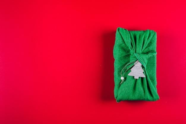 Cero desperdicio concepto de regalo de navidad. los regalos de furoshiki presentan una envoltura de tela de lino verde. eco amigable, concepto reutilizable. vista superior, espacio de copia
