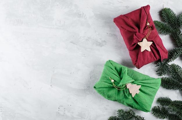 Cero desperdicio concepto de regalos de navidad. los regalos de furoshiki presentan un envoltorio con tela de lino verde y rojo. concepto ecológico y sostenible. vista superior, plano, copia espacio