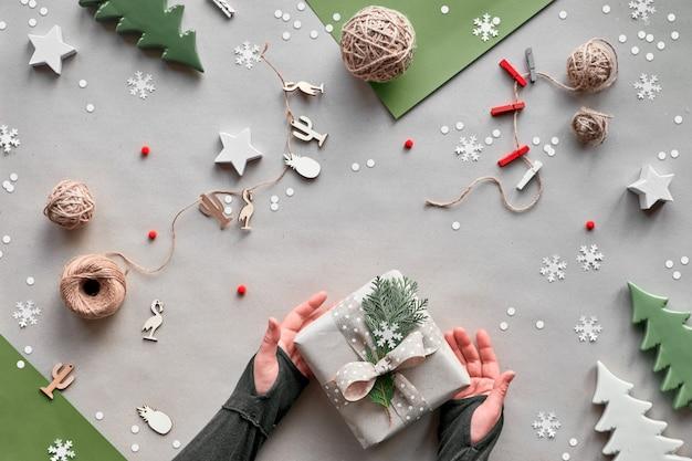 Cero desperdicio navidad, plano, vista superior sobre fondo de papel artesanal: guirnalda de muñecas textiles, regalos envueltos, manos decoran caja de regalo con cinta, lazo y ramita. eco amigable alternativa verde navidad.