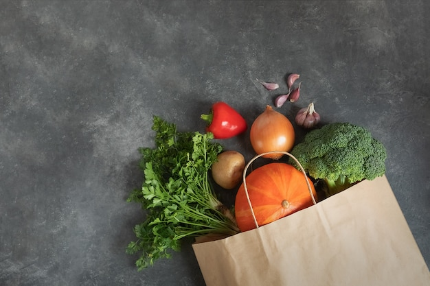 Cero desperdicio utiliza menos concepto de plástico. bolso de compras de papel lleno de verduras orgánicas frescas sobre fondo oscuro.