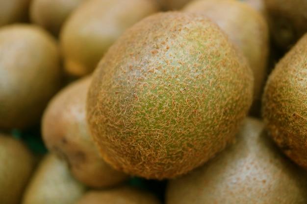 Cerrado con fruta fresca de kiwi en la borrosa pila de frutas kiwi