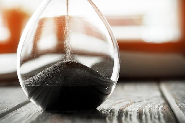 Cerrado de reloj de arena o reloj de arena en el fondo del libro