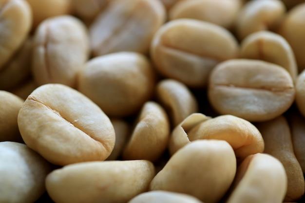 Cerrado hasta la textura de los granos de café sin tostar, fondo