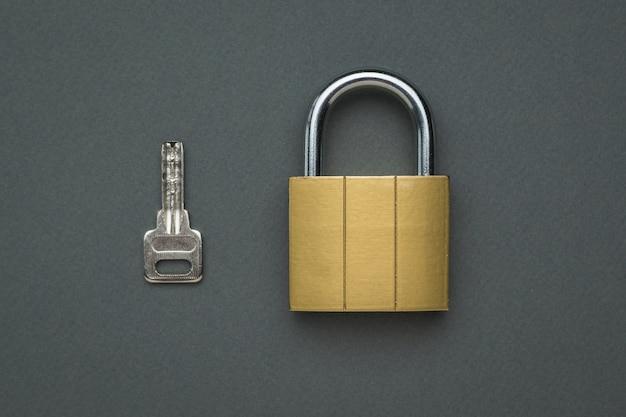 Cerradura clásica cerrada y llave sobre una mesa gris. el concepto de protección y seguridad. endecha plana.