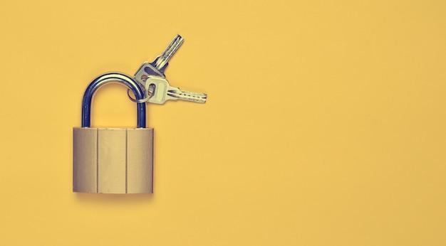 Cerradura dorada con llaves sobre un fondo amarillo