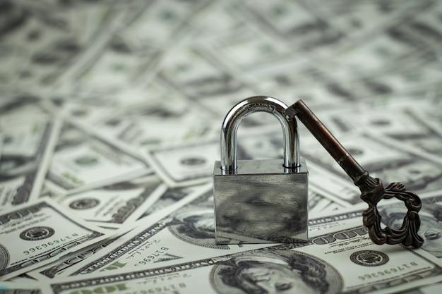 Cerradura de hierro y llave en la pila de dinero