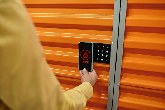 Cerradura inteligente. un trabajador de almacén probando el sistema de gestión digital