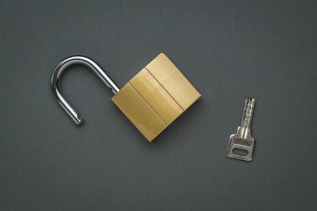 Una cerradura y una llave abiertas. el concepto de protección y seguridad. endecha plana.