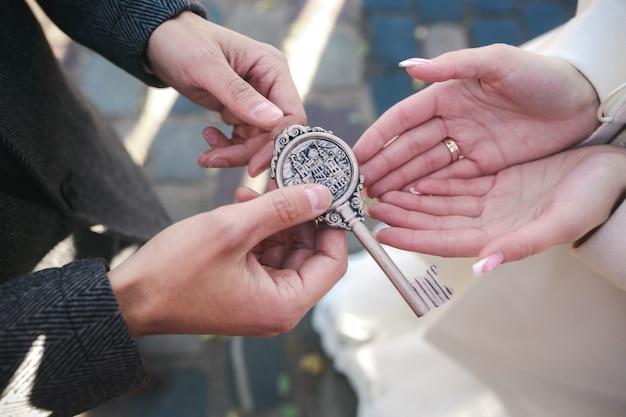 La cerradura con llaves en manos del novio y la novia.
