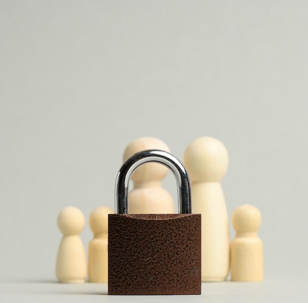 Cerradura de metal y una familia de figuras de madera sobre una superficie gris. concepto de seguridad, datos personales, información privada cerrada para el público.