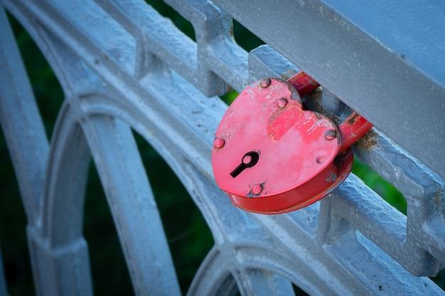 Cerradura roja de metal, bloqueada en una barandilla