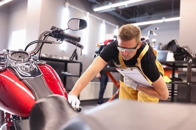 Cerrajero masculino diagnostica una motocicleta en el centro de servicio de mantenimiento del concepto de vehículos de motor
