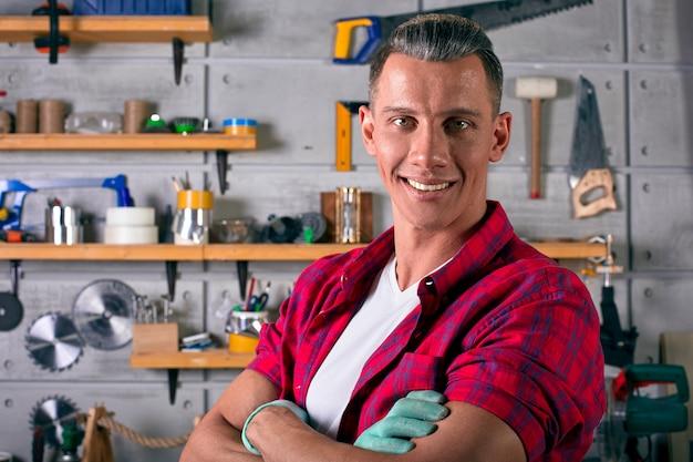 Cerrajero sonriente está de pie en el taller contra la pared de una pared con estantes para herramientas
