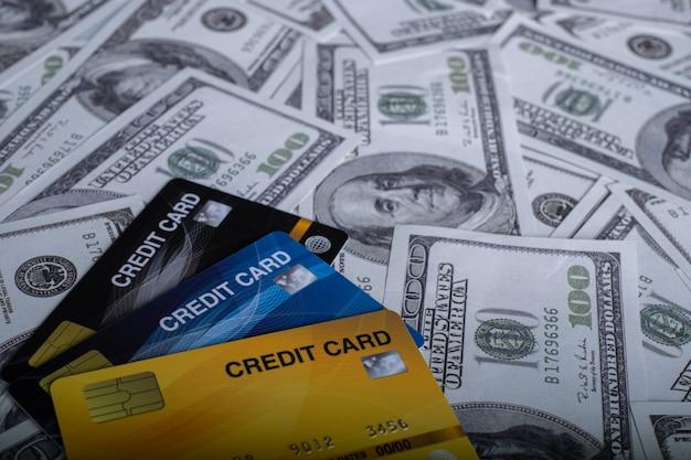 Cerrar 3 tarjetas de crédito aisladas en la pila de billetes de dinero de fondo de 100 usd