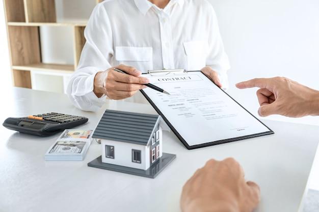 Cerrar agente inmobiliario presentando contrato al cliente