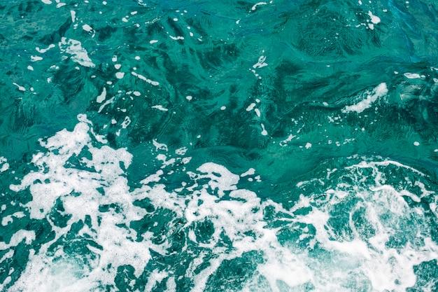 Cerrar el agua cristalina de tiro superior con olas