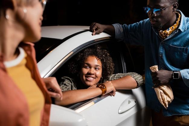 Cerrar amigos sonrientes con coche