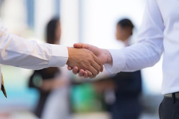 Cerrar, apretón de manos de dos hombres de negocios en el fondo de la oficina moderna, concepto de asociación