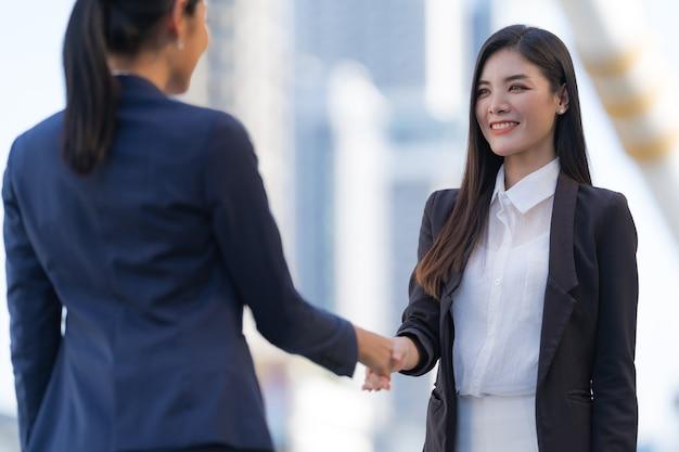 Cerrar, apretón de manos de dos mujeres de negocios en el fondo de la oficina moderna