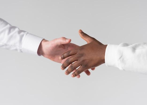 Cerrar un apretón de manos con fondo blanco.