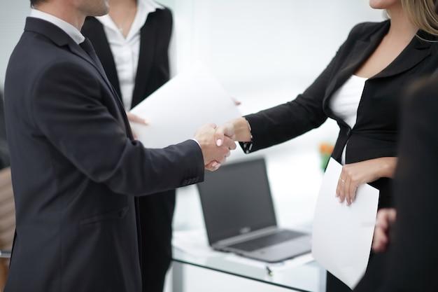 Cerrar apretón de manos de socios comerciales en el fondo de la oficina.