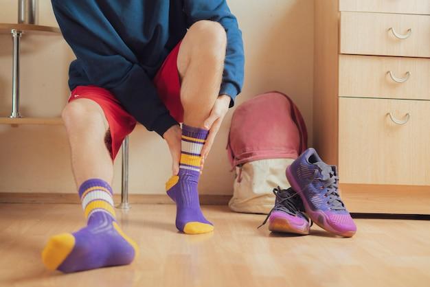 Cerrar atleta en vestuario ponerse calcetines y usar ropa deportiva