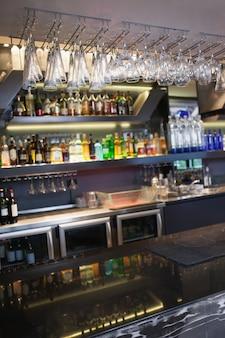 Cerrar en la barra con copas de vino colgando encima de él en la discoteca