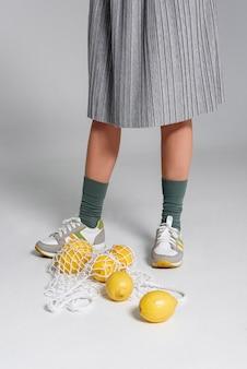 Cerrar bolsa de tortuga con limones al lado de pies de mujer