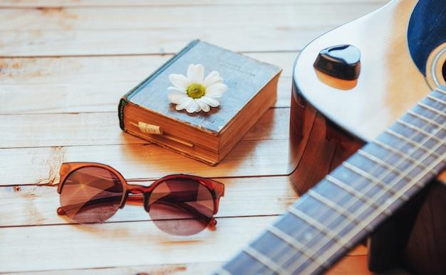 Cerrar la cabeza de guitarra clásica con gafas y libro