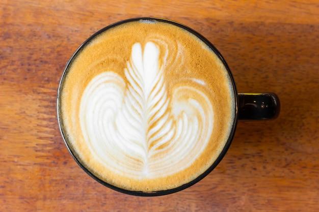 Cerrar café latte está en un vaso colocado sobre una mesa en la cafetería, hombre de negocios sentado tomando café en el escritorio, vista superior café con leche