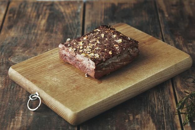 Cerrar la carne cuadrada a la parrilla con especias y sal aislado sobre tabla de madera en mesa vintage