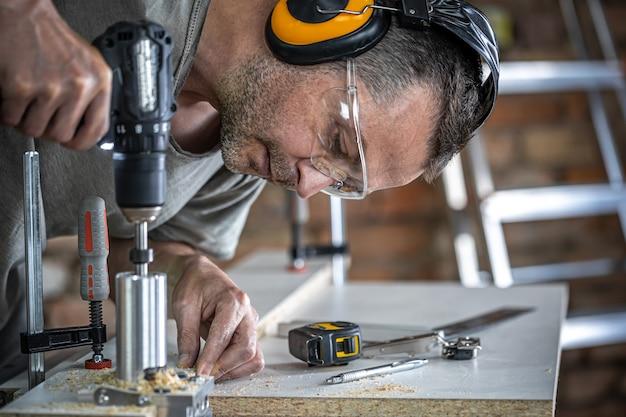 Cerrar un carpintero trabajando con madera y herramientas de construcción en casa